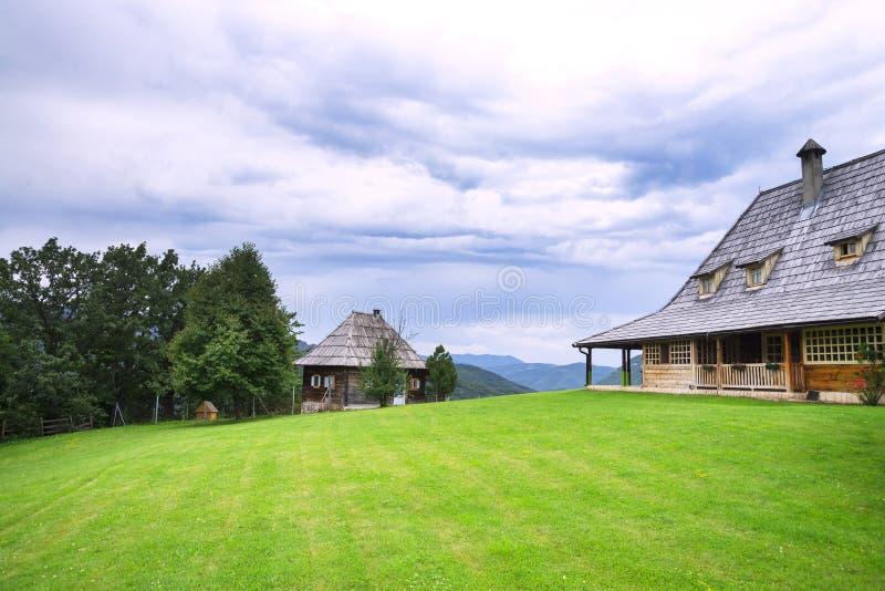 Позеленейте накошенный лужайке перед деревянным домом стоковая фотография rf