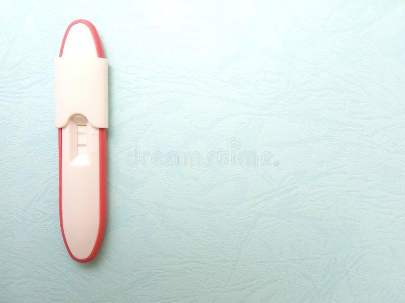 Позитивный результат пакета теста на беременность плоского положения фото пластиковый на texturized голубой бумажной предпосылке стоковое фото