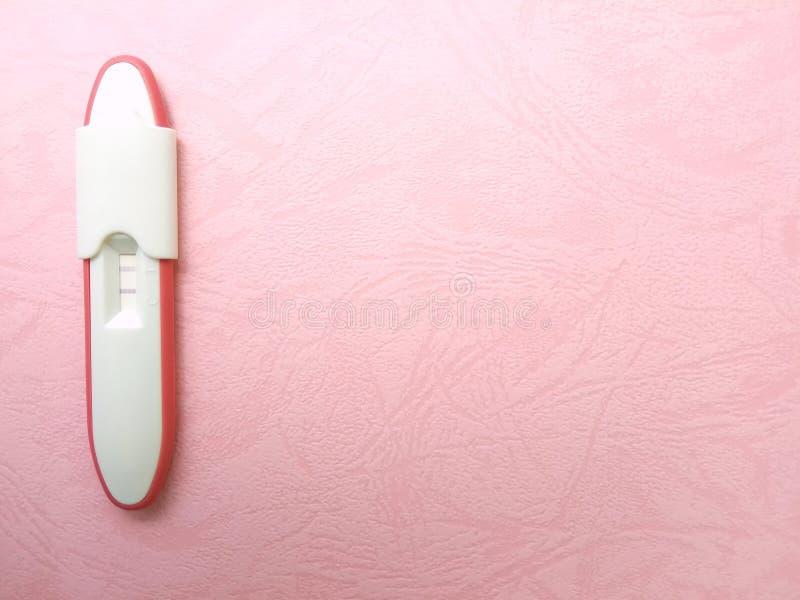 Позитивный результат пакета теста на беременность простого плоского положения пластиковый на texturized розовой бумажной предпосы стоковая фотография rf