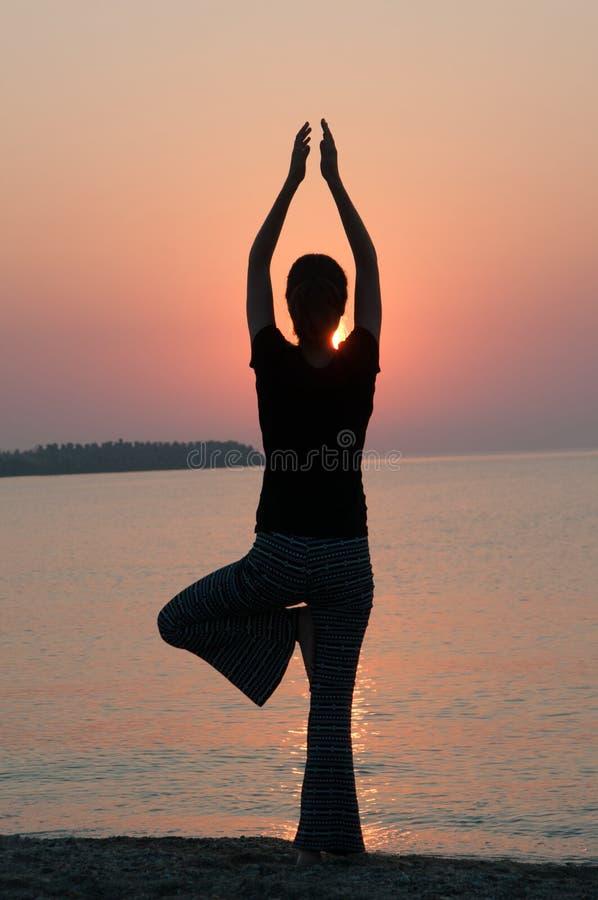 Позиция йоги захода солнца стоковое фото rf