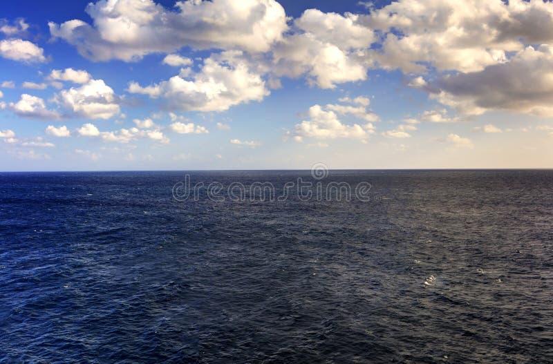 Поздно вечером фото HDR моря spanning полностью к горизонту и голубому свету облачного неба и красных солнца на праве стоковое фото rf