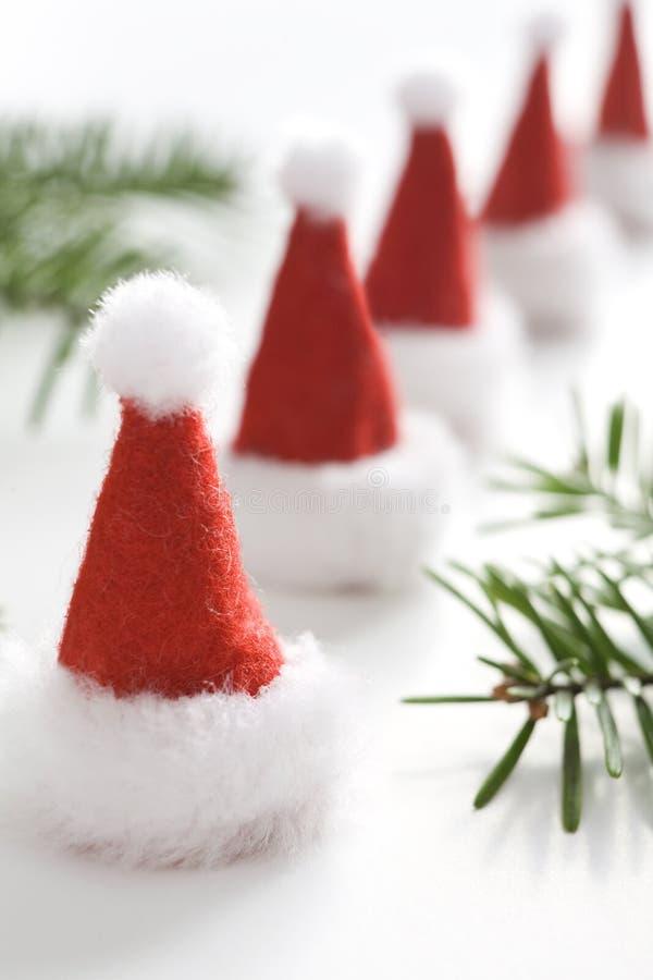 Поздравительная открытка рождества с малыми шляпами santa Одна большая шляпа santa стоковые изображения rf
