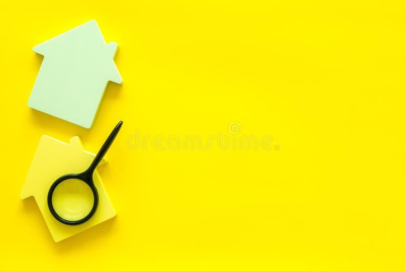Поиск для концепции нового дома с диаграммой и увеличителем дома на желтом космосе взгляда сверху предпосылки стола офиса для тек стоковые изображения rf