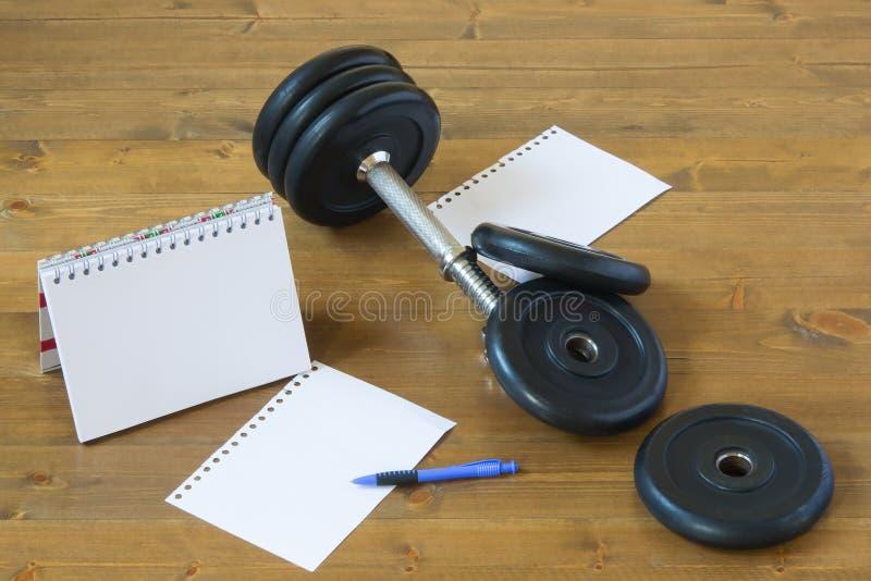 Показатели спорт на деревянной предпосылке, рядом с оборудованием фитнеса стоковое изображение