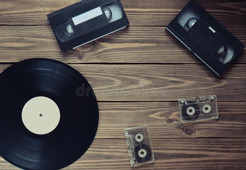 Показатель винила, видео- кассета, магнитофонная кассета на деревянной предпосылке Взгляд сверху Ретро технология средств массово стоковые фото