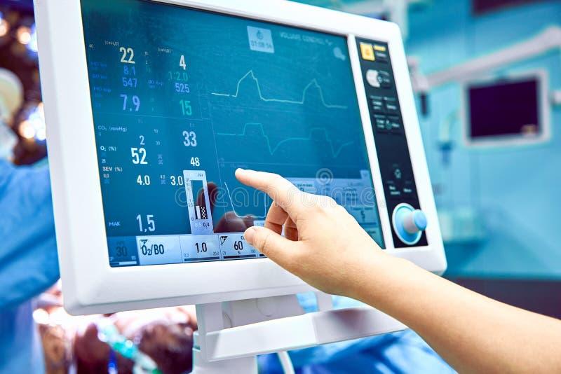 Показатель жизненно важных функций ` s контроля терпеливый в операционной доктор cheking на показателях жизненно важных функций п стоковое фото rf