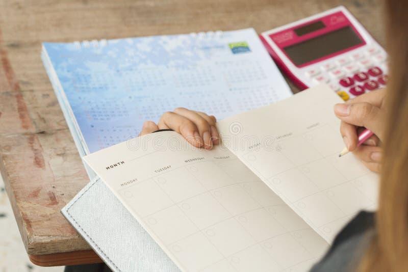 Показатель плановика тетради женщины работая ежемесячный для финансового стоковая фотография rf