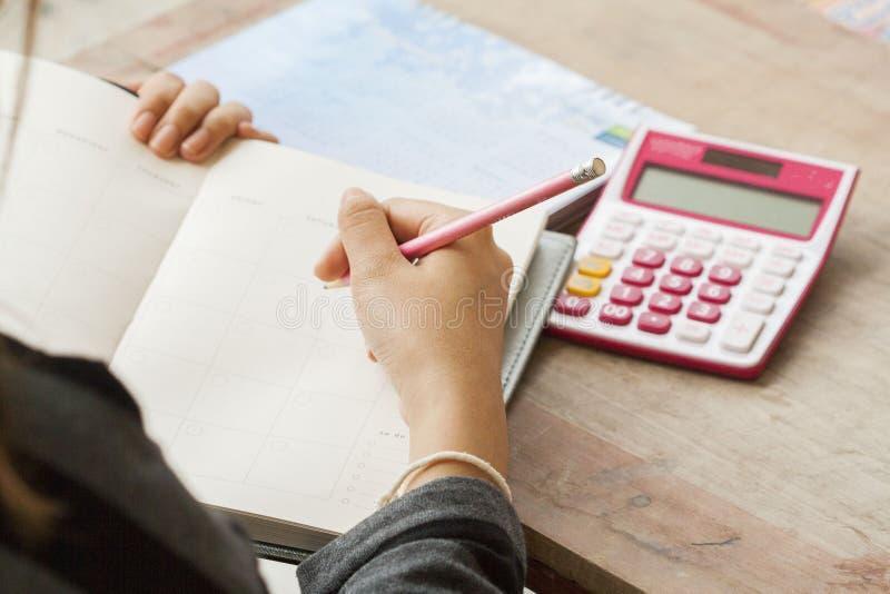 Показатель плановика тетради женщины работая ежемесячный для финансового стоковые фото
