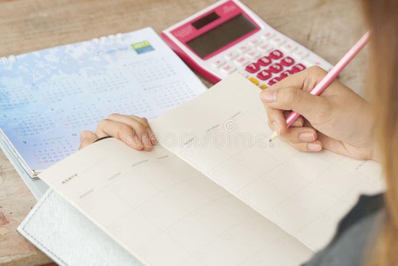 Показатель плановика тетради женщины работая ежемесячный для финансового стоковое фото rf