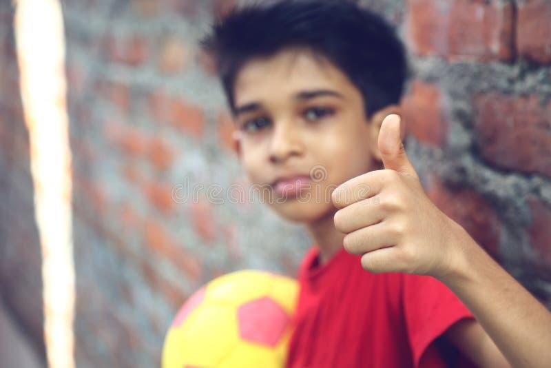 Показывать мальчика большие пальцы руки поднимает знак стоковые изображения rf