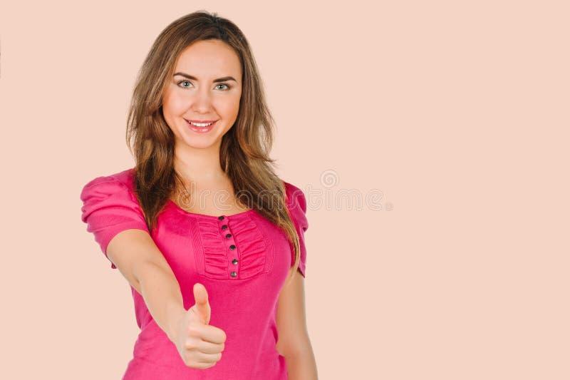 Показывать молодой женщины большие пальцы руки вверх стоковая фотография rf