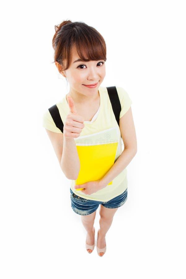 Показывающ большому пальцу руки красивого студента высокая угловая съемка стоковые фото