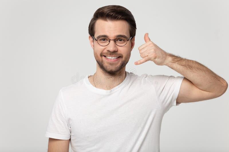 Показ Гай вызывает меня назад жестом со съемкой студии руки стоковое изображение