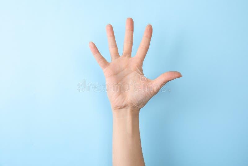 Показ 5 женщины на предпосылке цвета Язык жестов стоковые фото