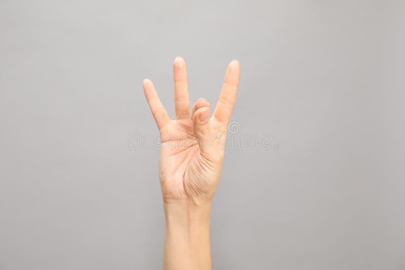 Показ 8 женщины на серой предпосылке Язык жестов стоковая фотография rf