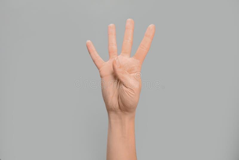 Показ 4 женщины на серой предпосылке Язык жестов стоковая фотография rf