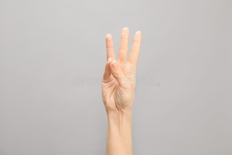 Показ 6 женщины на серой предпосылке Язык жестов стоковое фото rf