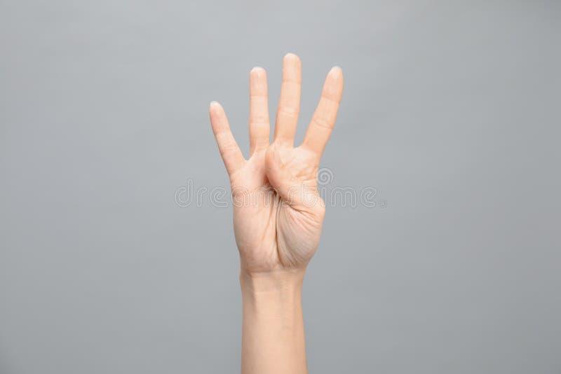 Показ 4 женщины на серой предпосылке Язык жестов стоковое изображение rf