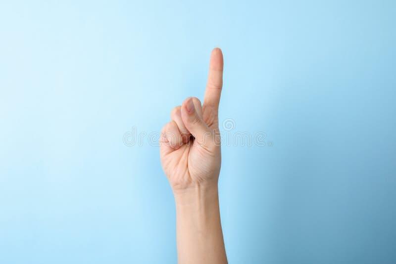 Показ одно женщины на предпосылке цвета, крупном плане стоковое фото rf
