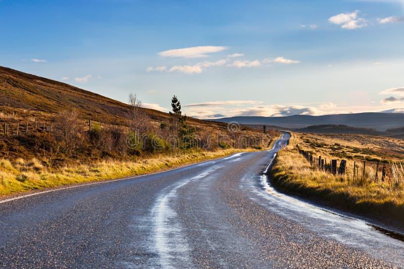 Покинутая дорога после ливня в гористых местностях в Шотландии стоковая фотография rf