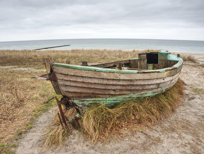 Покинутая разрушенная шлюпка вставленная в песке Старая деревянная шлюпка на песочном береге стоковые фотографии rf