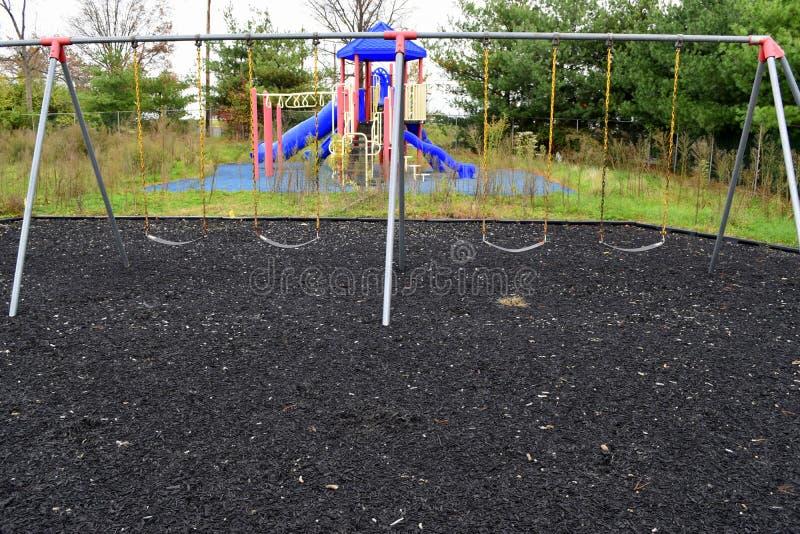 Покинутая спортивная площадка ` s ребенка с толстыми засорителями стоковое фото rf