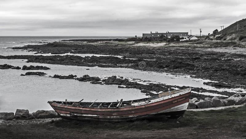 Покинутая шлюпка на суровой береговой линии стоковая фотография rf