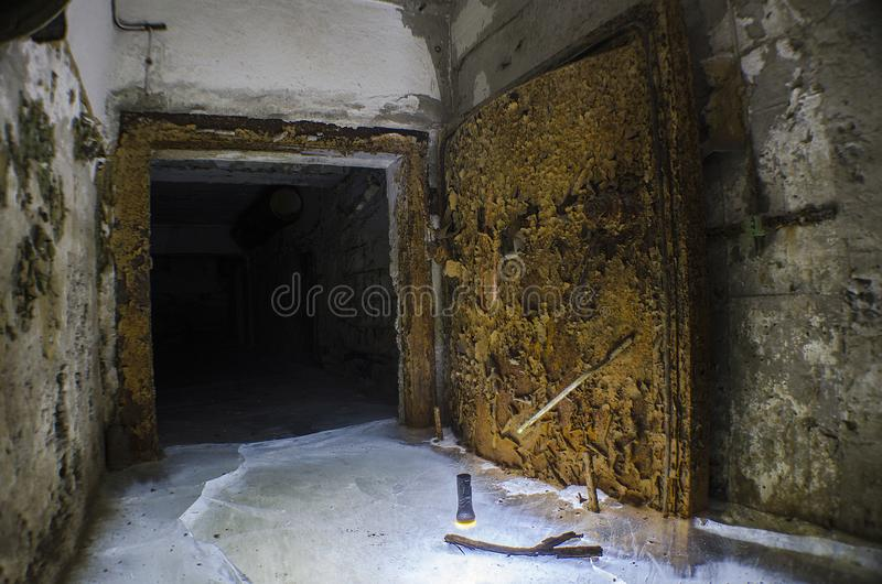 Покинутое затопленное укрытие бомбы в подвале, с ржавой воздухонепроницаемой дверью стоковое изображение rf