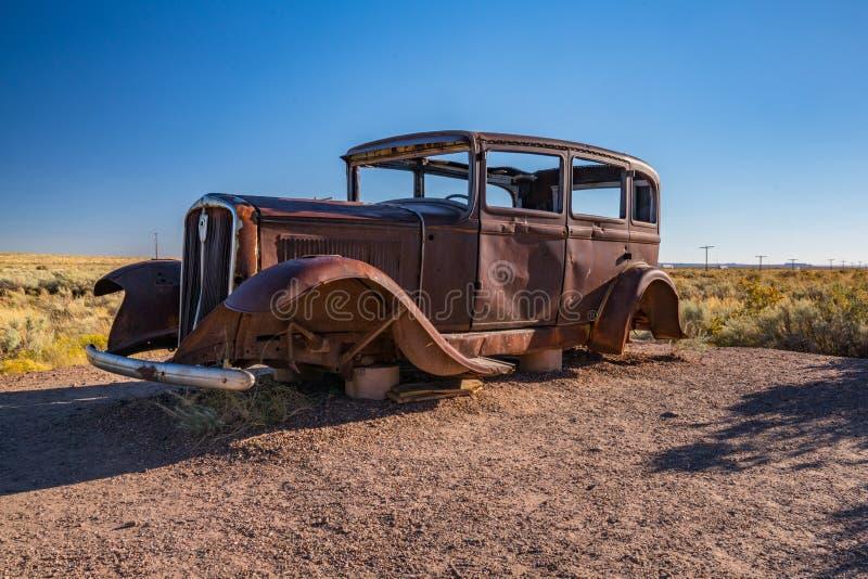 Покинутый автомобиль в окаменелом национальном парке леса вдоль трассы 66 стоковое фото rf