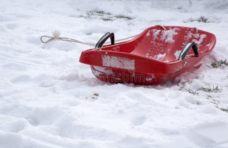 Покинутый красный бобслей на снеге стоковое фото rf