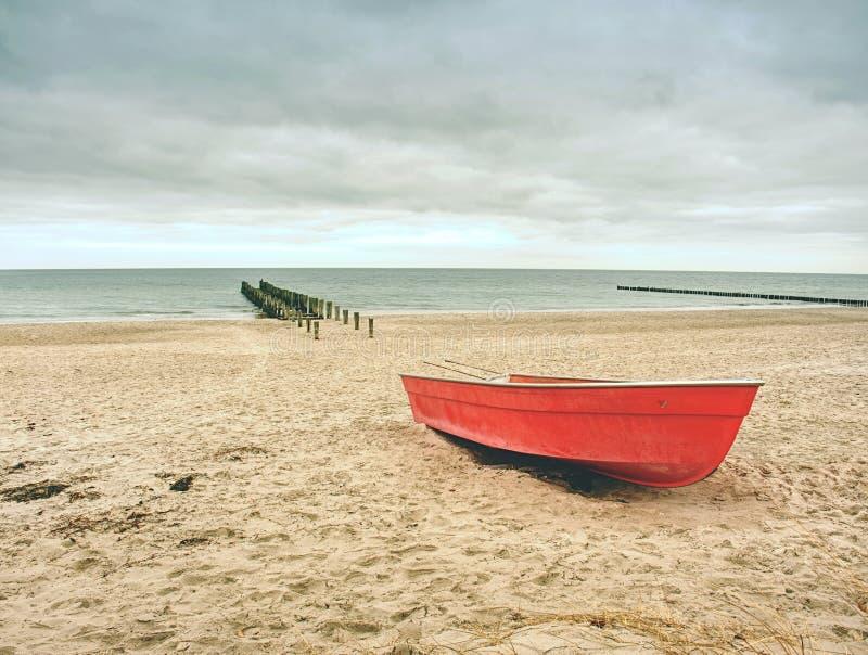 Покинутый удящ шлюпку затвора на песке залива моря Тихий уровень морской воды стоковое изображение