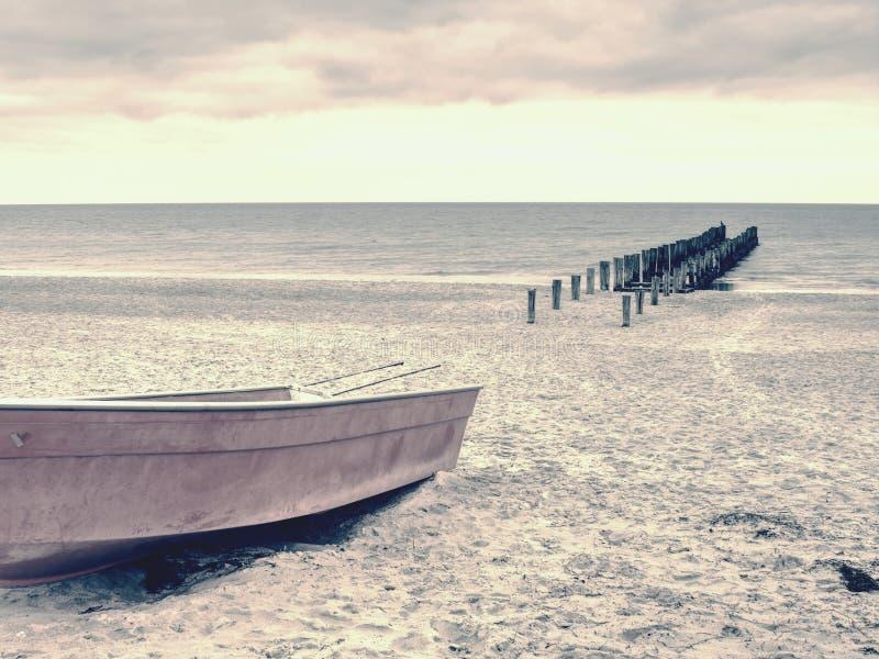 Покинутый удящ шлюпку затвора на песке залива моря Тихий уровень морской воды стоковые изображения