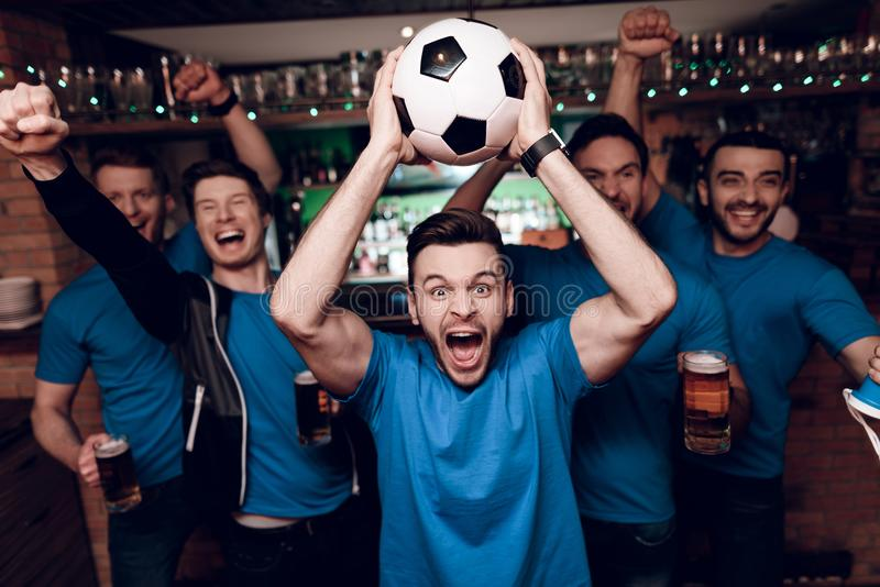 5 поклонников футбола выпивая пиво празднуя и веселя на баре спорт стоковые фотографии rf