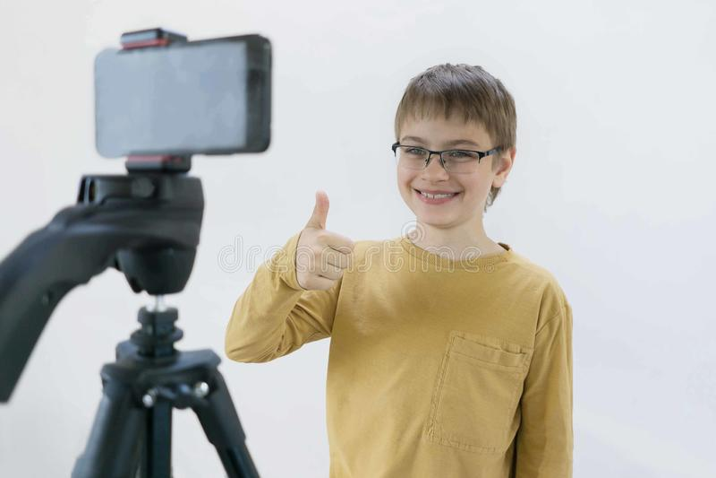 Поколение Milenium школьника стоит на бетонной стене в его доме и снимает видео для его канала для того чтобы положить дальше стоковое изображение rf