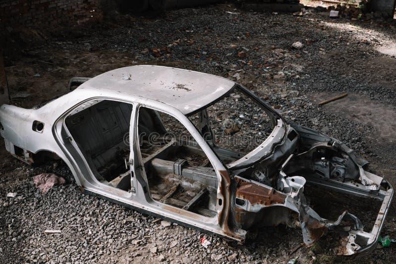 Поколоченное и ржавое серое тело автомобиля в месте захоронения отходов стоковые изображения rf