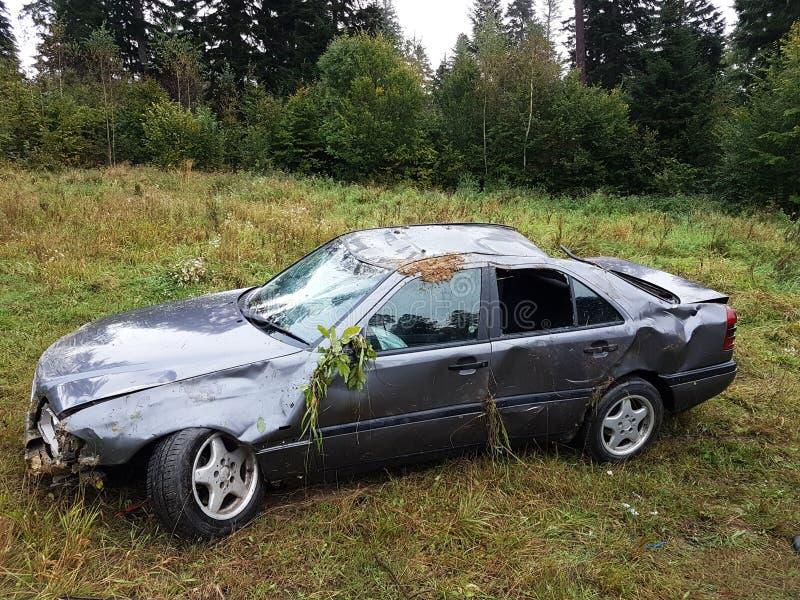 Поколоченный серый седан автомобиля лежит во рве обочины среди сочной зеленой листвы куста летом Случай дорожного движения стоковое изображение rf