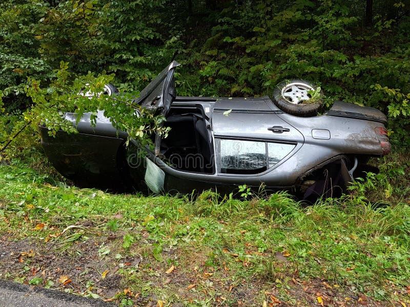 Поколоченный серый седан автомобиля лежит во рве обочины среди сочной зеленой листвы куста летом Случай дорожного движения стоковые изображения
