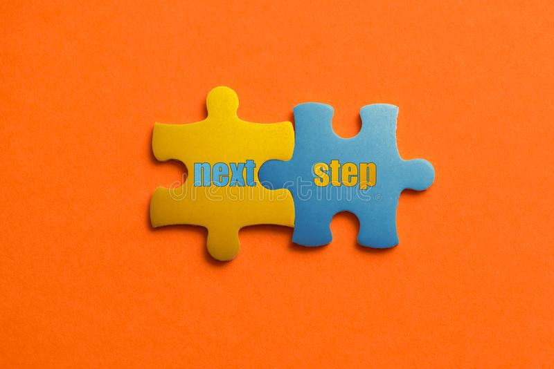 2 покрасили детали головоломки с следующим шагом текста на оранжевое поднимающем вверх предпосылки, желтых и голубых, близких стоковые фотографии rf
