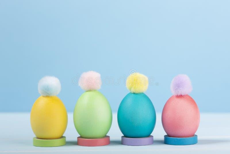 4 покрасили красочные яйца цыпленка пасхи в стойках с яркими помпонами стоковая фотография