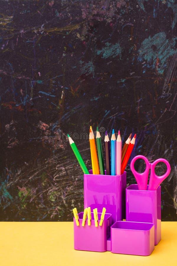 Покрасьте карандаши, ножницы и зажимы в стекле для канцелярских принадлежностей стоковая фотография