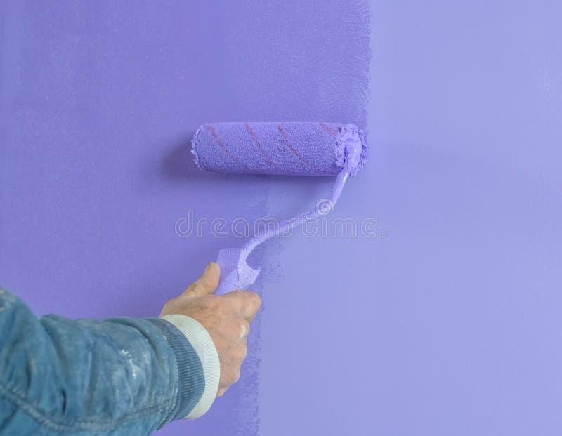 Покрасьте стены ролик в закрытой комнате стоковое изображение