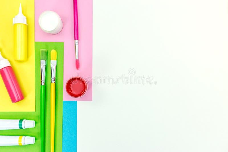 Покрашенная бумага альбома, краски акварели, щетки на белом ба стола стоковое фото
