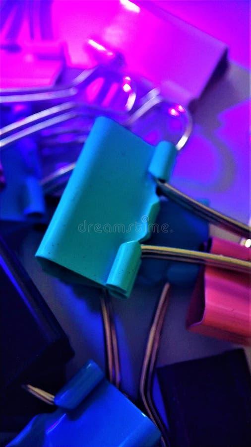 Покрашенные бумажные зажимы под лучами ультрафиолетов крупного плана макроса для предпосылки стоковая фотография