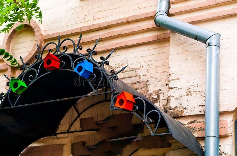 Покрашенные декоративные маленькие birdhouses на выкованной железной крыше против предпосылки кирпичной стены, естественного свет стоковые изображения