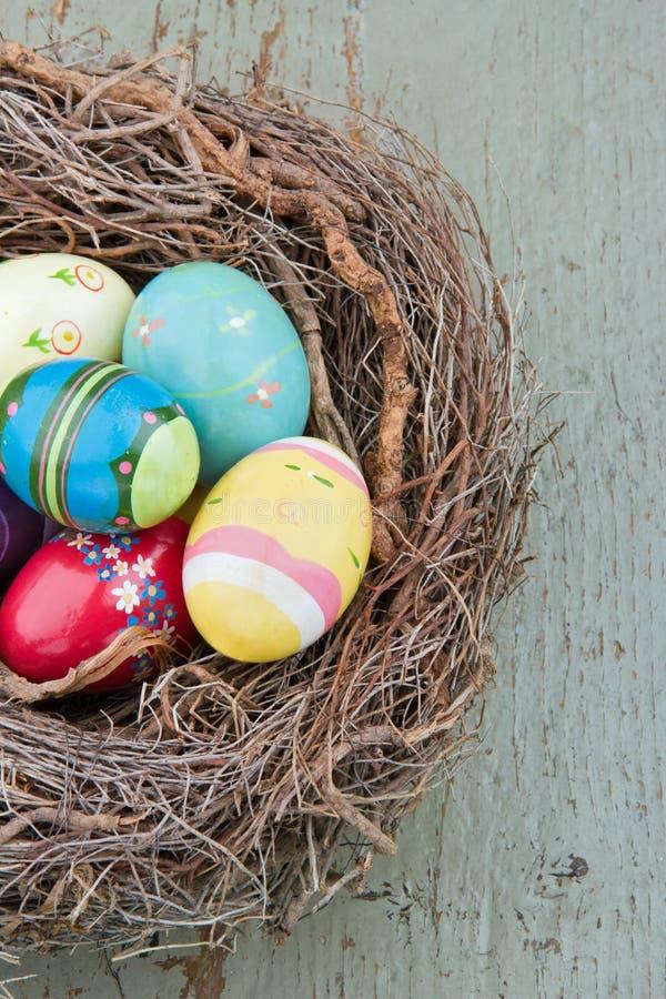 Покрашенные декоративные пасхальные яйца на деревянной предпосылке стоковые изображения