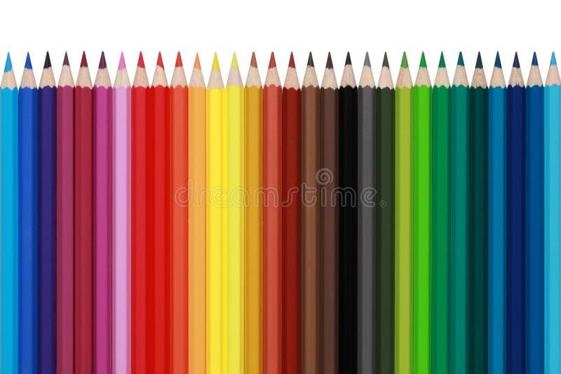 Покрашенные карандаши в изолированном рядке, стоковое изображение