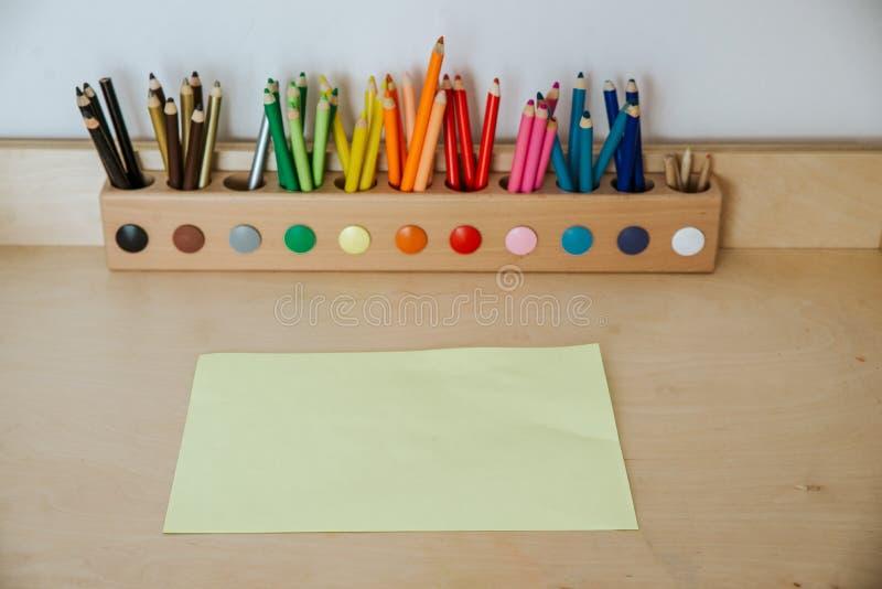 Покрашенные карандаши в контейнере на деревянном столе с бумагой стоковые изображения rf