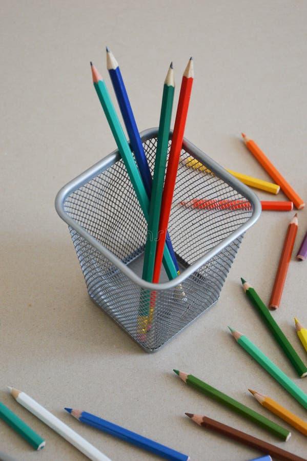 Покрашенные карандаши в сером стекле и на таблице стоковые изображения