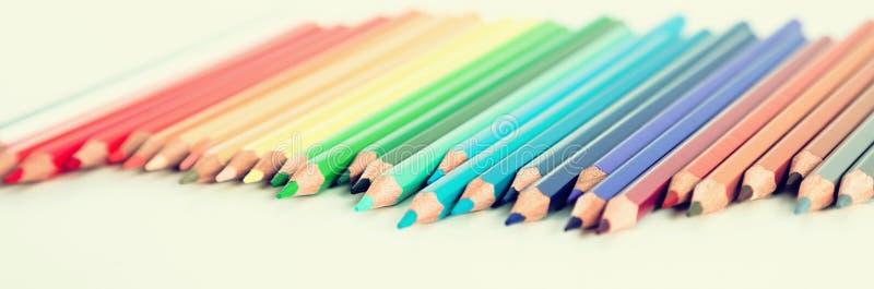 Покрашенные карандаши лежа в скачками строке стоковое фото rf