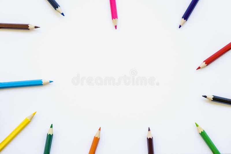 Покрашенные карандаши на белой бумаге, предпосылке альбома Концепция назад к школе Космос для текста стоковое изображение